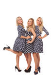 Three girls in dot dresses and black shoes Stock Photography