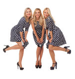 Three girls in dot dresses and black shoes Stock Images