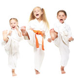 Three girls dressed in white kimono perform punch Stock Photography