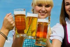Three girls drinking beer. Three beautiful girls in dirndl drinking beer Royalty Free Stock Image