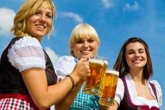 Three girls drinking beer. Three beautiful girls in dirndl drinking beer Stock Photography