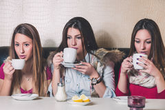 Three girls drinking hot beverage. In a cafe Royalty Free Stock Image