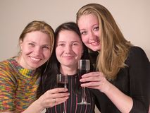 Three girls drinks wine Royalty Free Stock Photos