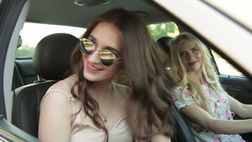 Three girls driving in a convertible car and having fun stock video