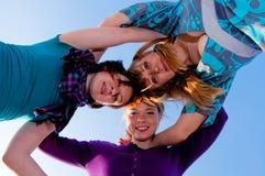 Three girls are embracing Stock Photo