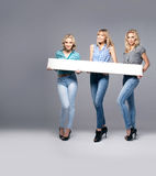 Three girls with empty board. Royalty Free Stock Image