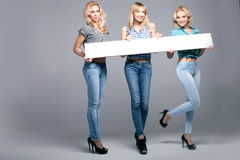 Three girls with empty board. Royalty Free Stock Photo
