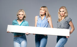 Three girls with empty board. Stock Photography