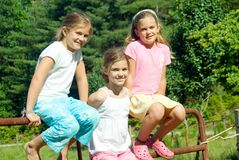 Three Girls on Fence/Triplets. These cute young girls sitting on a pasture fence are triplets stock image