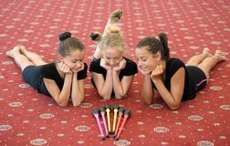Three girls on the floor looking at Indian clubs Royalty Free Stock Photo