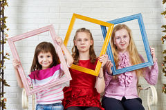 Three girls with frames of paintings Royalty Free Stock Photos