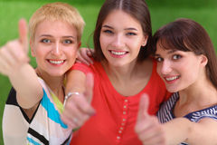 Three girls friends gesturing thumbs up Stock Photo