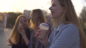 Three girls friends having fun on evening broadway. Eating ice cream, drinking ice fresh milk shake and chewing bubble stock footage