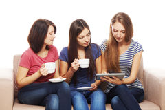Three girls friends using tablet. Sitting on sofa at home Stock Photos