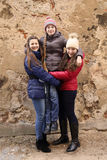 Three girls. Friendship and support concept - two bigger teenage girls  in winter clothes lifting up smaller one outdoor on old grunge wall background Stock Photo