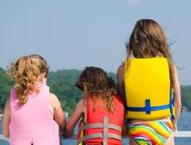 Three Girls on Front of Boat. Young girls standing at the bow of a pontoon boat looking out across the lake Royalty Free Stock Image