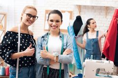 Three girls at garment factory. They are giving thumbs up finished new dress. stock photo