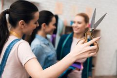 Three girls at garment factory. One of them is holding scissors. royalty free stock photo