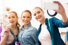 Three girls at garment factory. They are taking selfie desining new dress. royalty free stock photo