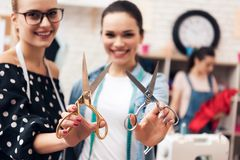 Three girls at garment factory. Two of them holding pairs of scissors. royalty free stock photo