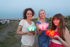 Three girls are getting ready to launch water lanterns Stock Photo