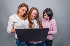Three girls girlfriends, looking  laptop  on a Royalty Free Stock Images