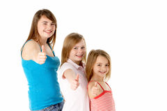 Three Girls Giving Thumbs Up Gesture In Studio Stock Photos