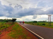 Three girls are going by cycle on a road. stock images