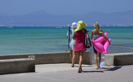 Three girls going to the beach. PLAYA DE PALMA, MAJORCA, SPAIN - JULY 24, 2013: Three girls go to the beach on the scorching hot day of July 24, 2013 in Playa de Royalty Free Stock Images