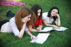 Three girls on the grass ready for lessons. Three girls on the grass in the summer preparing for the lessons Royalty Free Stock Photography