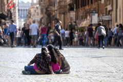 Three girls on the ground and tourists Stock Images