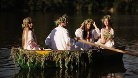Three girls and a guy in the Slavic national dress floating in a boat. Girls in wreaths in a boat. national tradition stock video footage