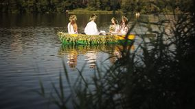 Three girls and a guy in the Slavic national dress floating in a boat. Girls in wreaths in a boat. national tradition stock footage