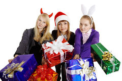 Three girls hand over New Year's gifts. Isolated on a white background Royalty Free Stock Images