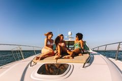 Three girls hanging out on a private yacht deck. Three girls sitting on the deck of a private yacht in the sea. Smiling female friends in swimsuits relaxing on Stock Photos
