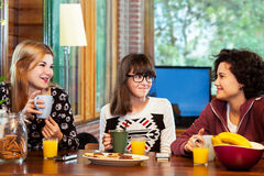 Three girls having breakfeast at home. Royalty Free Stock Photos