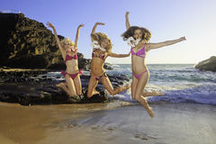 Three girls at a hawaii beach. Three girls in bikinis at a hawaii beach wearing flower leis and jumping Stock Images