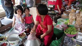 Three girls are helping to train local baker to sell to tourists who travel in the market in Thailand. Ayutthaya, Thailand - Feb 22, 2015:Three girls are helping stock video footage