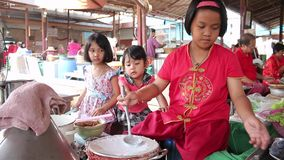 Three girls are helping to train local baker to sell to tourists who travel in the market in Thailand. Ayutthaya, Thailand - Feb 22, 2015:Three girls are helping stock footage