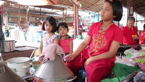 Three girls are helping to train local baker to sell to tourists who travel in the market in Thailand. Ayutthaya, Thailand - Feb 22, 2015:Three girls are helping stock video