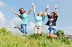 Three girls holding hands jumping on summer field Stock Photo