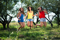 Three girls holding hands jumping on summer garden. Three beautiful young ladies holding hands jumping on summer garden outdoors background Royalty Free Stock Photos