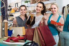 Three girls holding a paper shopping bags in the boutique royalty free stock photo