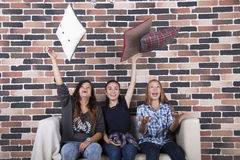 Three girls at home party throwing pillows up Royalty Free Stock Image