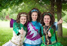 Three girls in irish dance dresses showing thumbs up Stock Image
