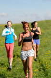 Three girls jogging downhill summer meadow. And smiling Stock Photo
