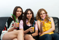 Three girls with juice glasses Royalty Free Stock Photography