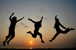 Three girls jump as their freedom expression. Morning happiness and freedom on sunrise at beach Stock Photos