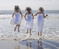 Three Girls Jumping. Three young girls wearing matching white dresses jumping in the waves at the ocean Stock Photography