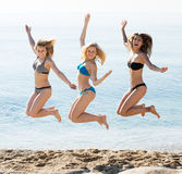Three girls jumping on beach stock image